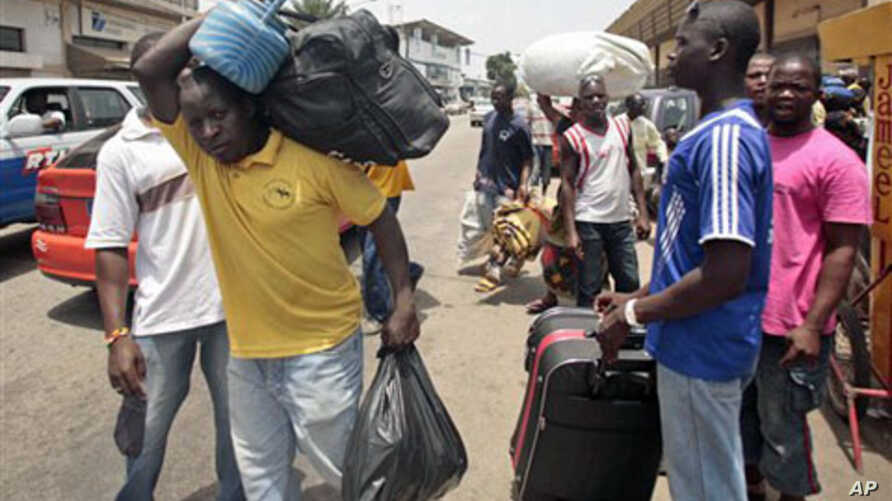 People walk with their belongings towards a railway station as they leave Abidjan, Ivory Coast. Rebel forces backing Ivory Coast's internationally recognized president were advancing toward the capital Wednesday, March 29, 2010