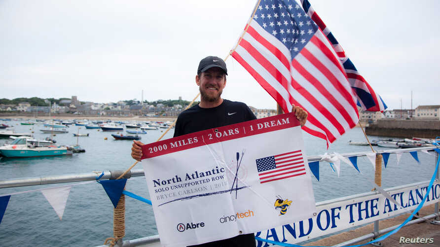 Bryce Carlson, a high school biology teacher, rowing coach and endurance athlete from Cincinnati, Ohio, U.S.A., holds a banner, after completing a solo, unassisted row across the North Atlantic Ocean, upon his arrival at St. Mary's, on the Isles of S