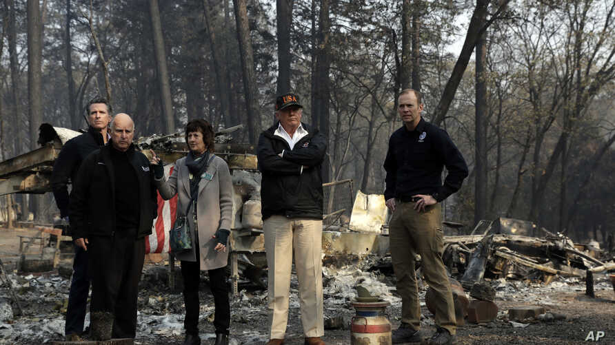 President Donald Trump talks with from left, Gov.-elect Gavin Newsom, California Gov. Jerry Brown, Paradise Mayor Jody Jones and FEMA Administrator Brock Longduring a visit to a neighborhood destroyed by the wildfires, Saturday, Nov. 17, 2018, in Par