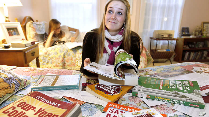 FILE -  Kim Pollock, 17, facing center, goes through college materials, with the help of her sister Lindsay, 15, back left, in her bedroom in Bedford, N.H.