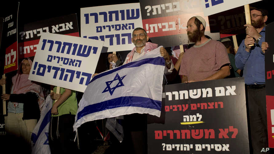 FILE - Israeli politician Michael Ben Ari, center, holds an Israeli flag while attending a demonstration against the release of Palestinian prisoners from Israeli jails, outside the Ofer military prison near the West Bank city of Ramallah, Oct. 29, 2