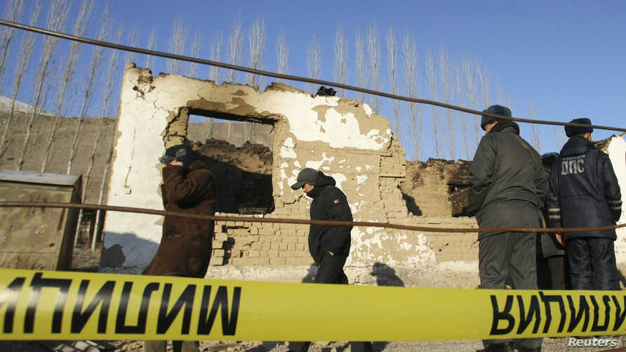 FILE - Security personnel inspect the site of a raid in the village of Besh-Kungei outside Bishkek, Kyrgyzstan, conducted as part of a military operation against suspected Islamist militants.