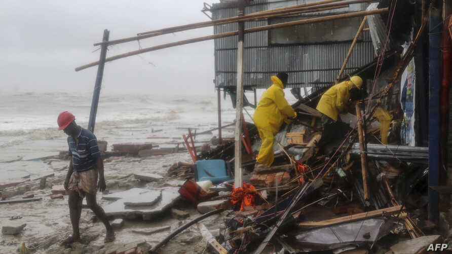 Bangladeshi rescue workers search for survivors after Cyclone Roanu hit Chittagong, May 21, 2016. Cyclone Roanu struck the Bangladesh coast forcing hundreds of thousands to flee their homes as the storm unleashed strong winds and heavy rains.