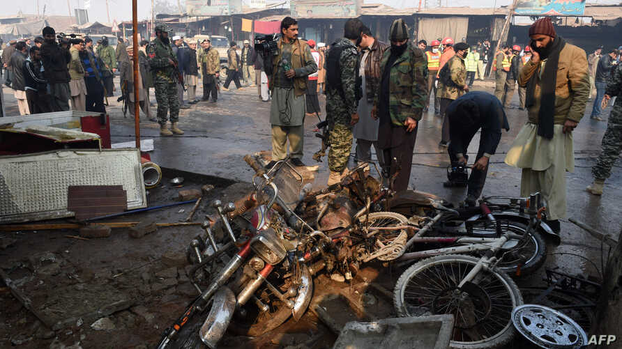 Pakistani security officials examine the site of a suicide bomb attack on the outskirts of Peshawar, Jan. 19, 2016. At least 12 people were killed in a suicide attack on a market during morning rush hour in the outskirts of the northwestern city, off
