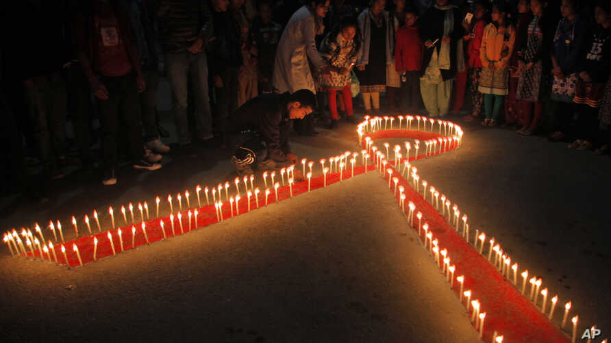 """Nepalese women and children from """"Maiti Nepal"""", a rehabilitation center for victims of sex trafficking, light candles on the eve of World AIDS Day in Kathmandu, Nepal, Monday, Nov. 30, 2015."""