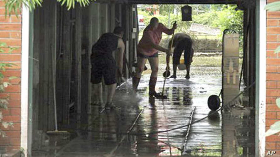 Local residents clear away the mud from their flooded home in Brisbane, Australia.  Parts of Brisbane reopened as deadly floodwaters that had swamped entire neighborhoods recede, revealing streets and thousands of homes covered in a thick layer of pu