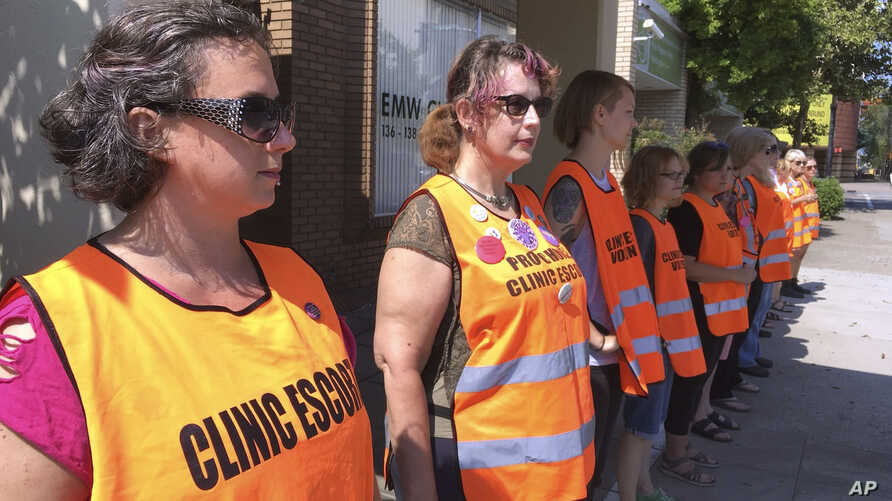 FILE - Escort volunteers line up outside the EMW Women's Surgical Center in Louisville, Ky., July 17, 2017. In a setback for Kentucky's Republican governor, a federal judge has struck down a state law requiring abortion clinics to have written agreem