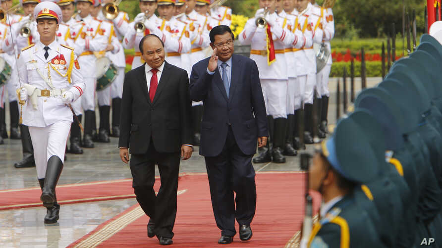 FILE - Cambodian Prime Minister Hun Sen, center right, and his Vietnamese counterpart Nguyen Xuan Phuc, center left, review an honor guard in Hanoi, Vietnam, Tuesday, Dec. 20, 2016. Hun Sen was in Vietnam for a two-day visit aimed at boosting relatio