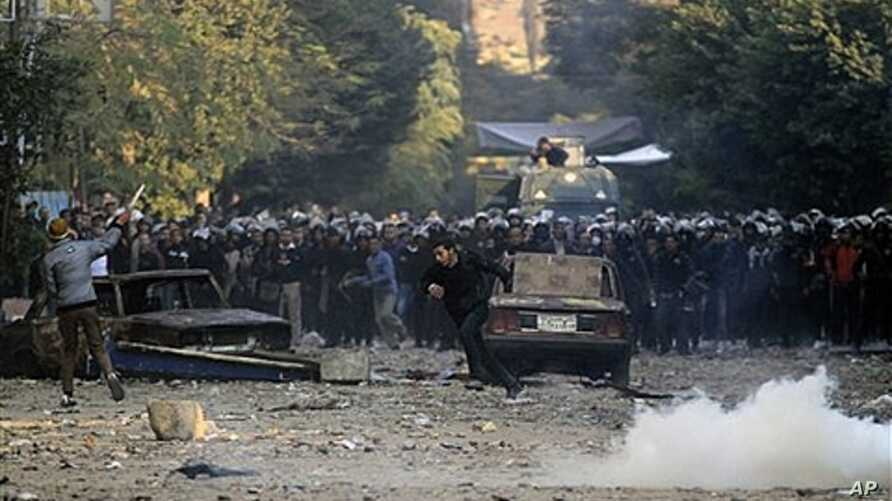 Protester runs for cover during clashes with Egyptian riot police, Cairo, Nov. 21, 2011.