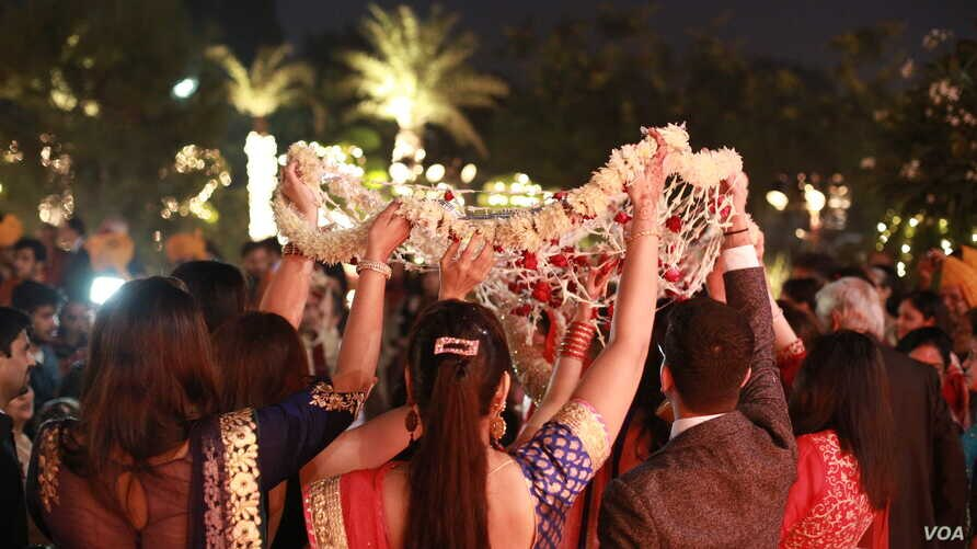 Brides arrive beneath a canopy of flowers for the wedding ceremony. (A. Pasricha/VOA)