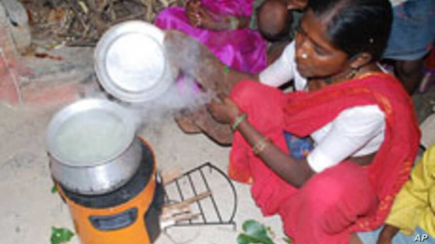 A woman in India is uses a cookstove that produces less smoke for burning wood or any other fuel.