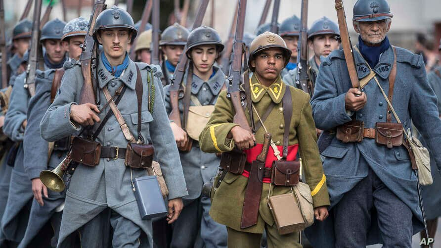Men dressed in WWI uniforms march during a parade, part of a reconstruction of the WWI battle of Verdun, Aug. 25, 2018, in Verdun, eastern France.