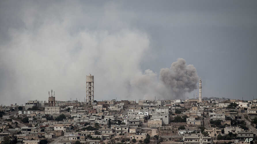 FILE - Smoke rises after a TNT bomb was thrown from a helicopter, hitting a rebel position during heavy fighting between troops loyal to Syrian President Bashar al-Assad and opposition fighters, near Kafr Nabuda, Idlib province, Syria, Sept. 19, 2013...