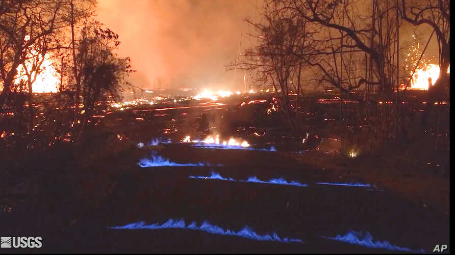 This photo from video from the U.S. Geological Survey shows blue flames of methane gas erupting through cracks on Kahukai Street in the Leilani Estates neighborhood of Pahoa on the island of Hawaii during the overnight hours of May 23, 2018.