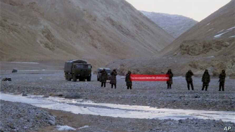 "Chinese troops hold a banner which reads: ""You've crossed the border, please go back"" in Ladakh, India on  May 5, 2013. India and China have agreed to end a three-week stand-off over their disputed Himalayan border."