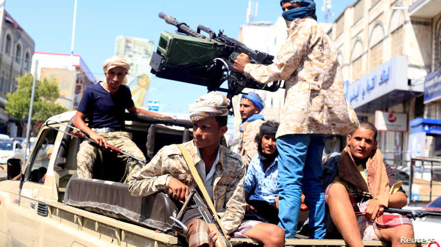 FILE - Government soldiers ride on the back of a patrol truck on a street where people demonstrated against the deterioration of Yemen's economy and the devaluation of the local currency.