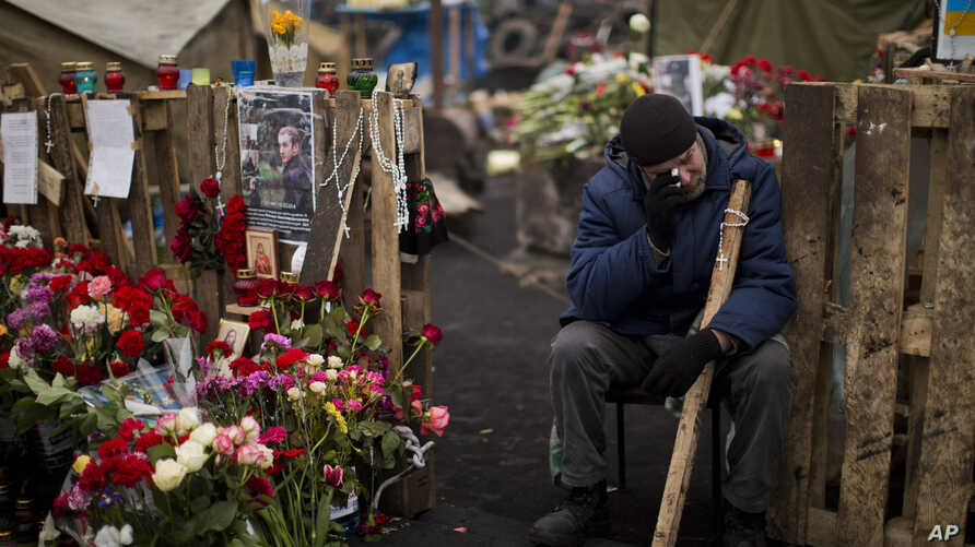 An anti-Yanukovych protester cries near a memorial for the people killed in clashes in Kyiv's Independence Square, Feb. 25, 2014.