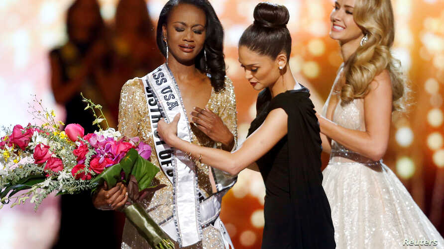 Deshauna Barber (L) of the District of Columbia reacts as Miss Universe 2015 Pia Wurtzbachshe gives her the winner's sash during the 2016 Miss USA pageant at the T-Mobile Arena in Las Vegas, Nevada, U.S., June 5, 2016.