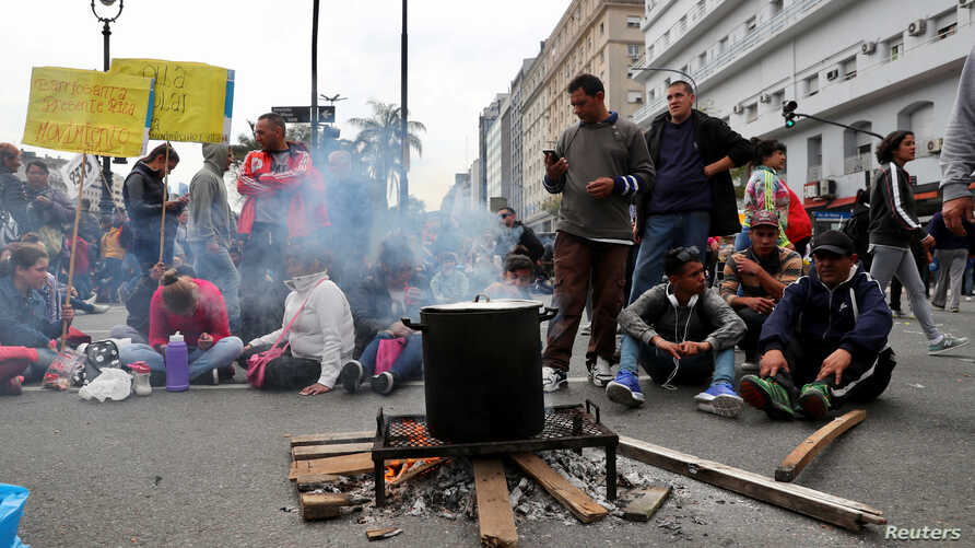 People wait to receive a free meal at a soup kitchen set up on 9 de Julio avenue during a demonstration against the government's economic measures in Buenos Aires, Argentina Sept. 12, 2018.