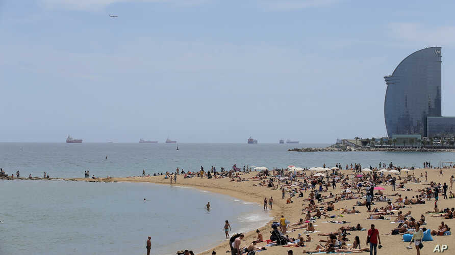 FILE - In this May 25, 2016 photo, people sunbathe at the Barceloneta beach in Barcelona, Spain.