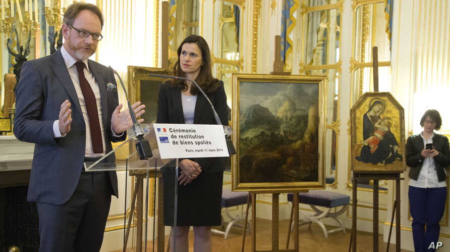 Great grandson of Richard Soepkez, Romanian Ion Florescu, left, speaks during a ceremony to return three paintings taken from their owners during World War ll, while France's culture minister Aurelie Filipetti, stands next to him at the Culture Minis