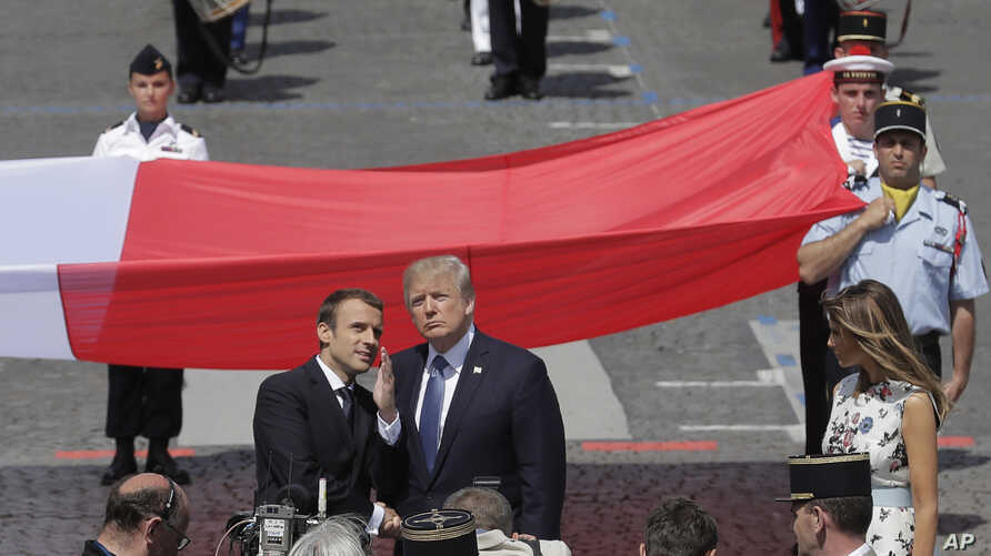 French President Emmanuel Macron talks with President Donald Trump next to a huge French flag after the Bastille Day parade in Paris, July 14, 2017.