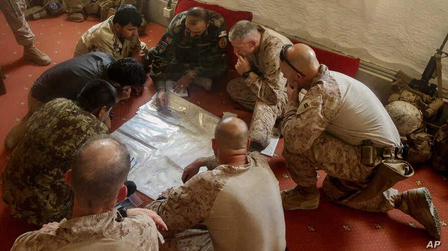 A photo released by Operation Resolute Support headquarters shows US Marines with Task Force Southwest and Afghan National Army soldiers planning for the continuation of offensive combat operations at Camp Hanson, Afghanistan, June 13, 2017.