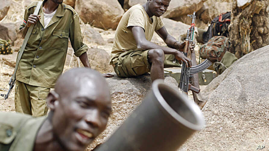 SPLA-N fighters practice with a mortar as others watch near Jebel Kwo village in the rebel-held territory of the Nuba Mountains in South Kordofan, Sudan May 2, 2012.