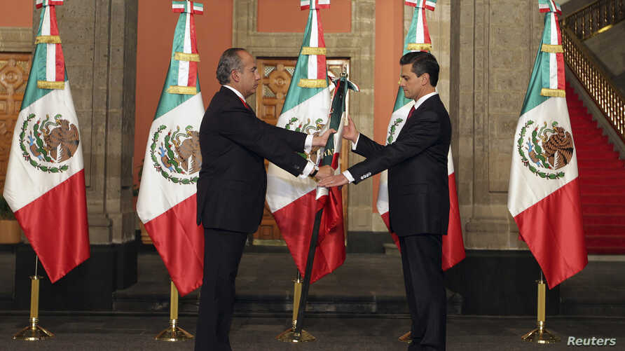 Mexico's outgoing President Felipe Calderon (L) hands the national flag to Mexico's new President Enrique Pena Nieto during a midnight ceremony at the National Palace in Mexico City December 1, 2012.