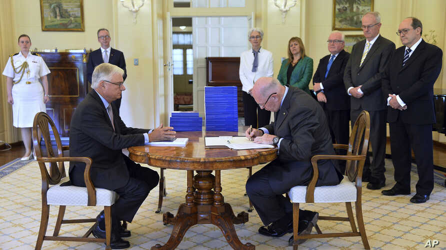 Commissioner Justice Peter McClellan, seated left, watches as Governor-General of Australia Peter Cosgrove, seated right, signs a document after receiving the final report of the Royal Commission into Institutional Responses to Child Sexual Abuse at