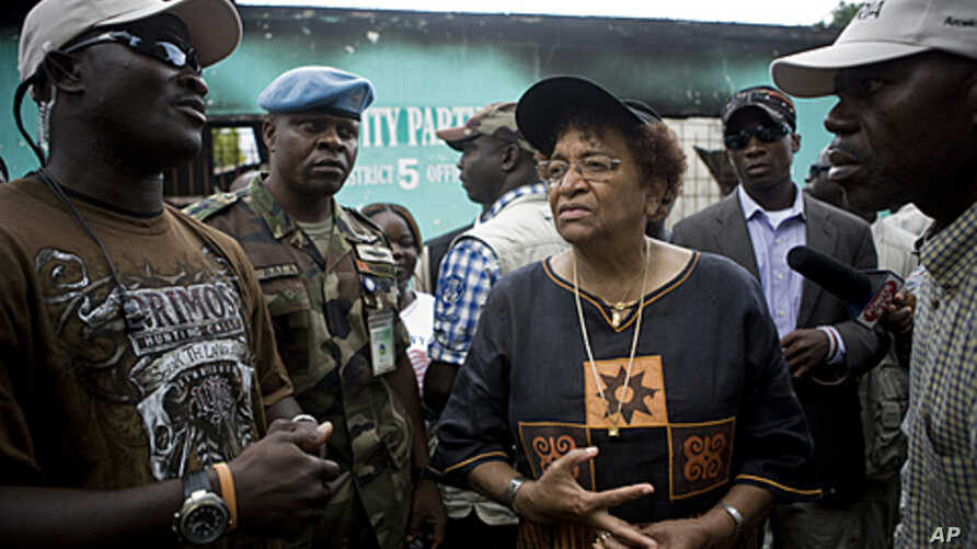 Liberian President Ellen Johnson Sirleaf (L) addresses a crowd of supporters outside offices of her party on the outskirts of Monrovia, October 15, 2011.