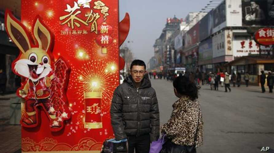 A Chinese couple takes a rest next to a new year decoration on displayed along a shopping district in Beijing, Feb 15, 2011