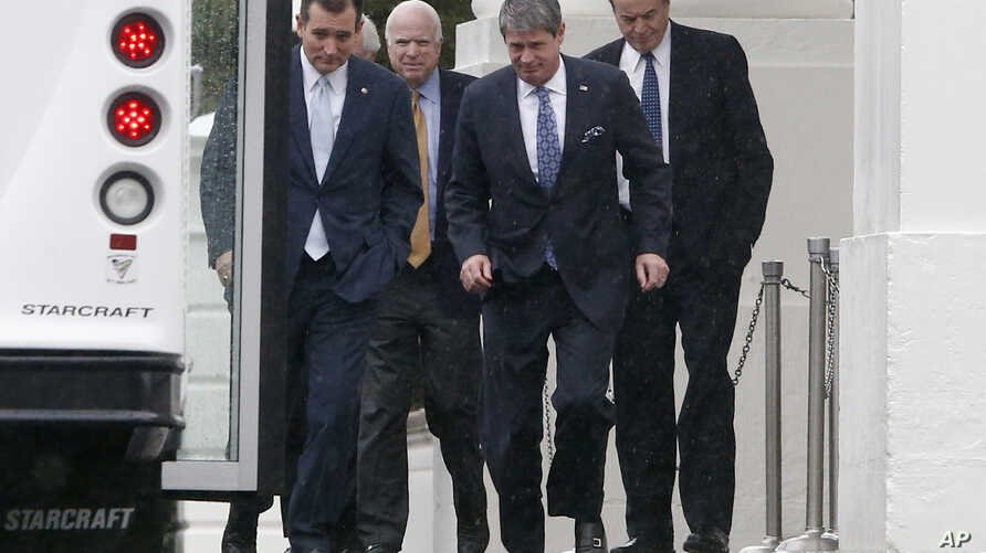 Republican senators walk in the rain back to their bus at the North Portico of the White House in Washington, Oct. 11, 2013.