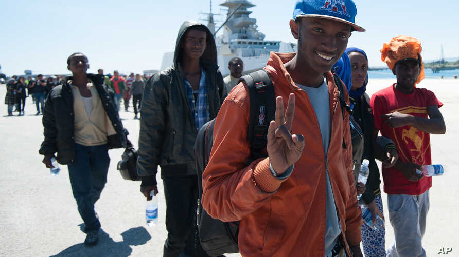 """A rescued migrant shows the victory sign after disembarking from the Italian Navy vessel """"Bettica"""" at Augusta, Sicily, southern Italy, April 22, 2015."""
