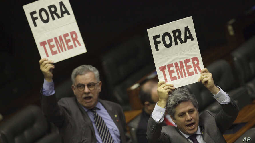 """Deputies from opposition parties carry signs that read in Portuguese """"Temer Out,"""" during a key vote by the lower chamber of Brazil's Congress on whether to suspend Brazil's President Michel Temer and put him on trial over an alleged bribery scheme, i"""