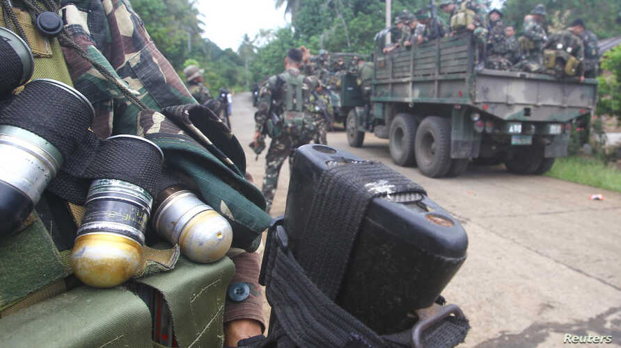 Soldiers stand guard on a road as they are deployed to remote villages in Jolo, Sulu southern Philippines, Oct. 17, 2014.