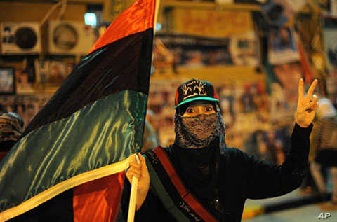 A Libyan woman carrying the flag of the old Libyan monarchy flashes a V for victory sign during a gathering against Libyan leader Moammar Gadhafi at Revolution Square in Benghazi, May 17, 2011
