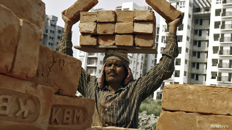 FILE - A laborer stacks bricks on his head at the construction site of a residential complex in Kolkata, Feb. 28, 2015.