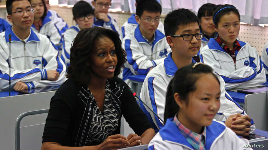 U.S. first lady Michelle Obama (L) sits in for an English class with students at Chengdu No. 7 High School during her visit in Chengdu, Sichuan province, March 25, 2014.