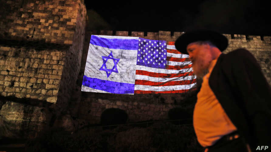 A picture taken on December 6, 2017 shows a giant US flag screened alongside Israel's national flag by the Jerusalem municipality on the walls of the old city.
