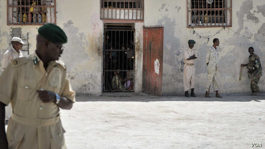 FILE - Prison guards stand outside a cell in Mogadishu Central Prison, December 10, 2013.