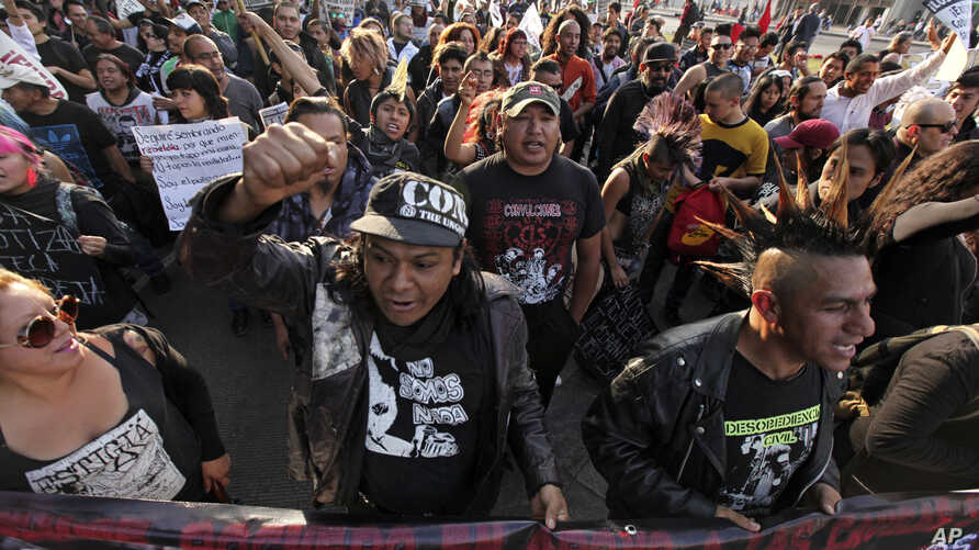 Protesters from an anarchist group shout slogans as they march against fuel price hikes in Mexico City, Jan. 9, 2017.