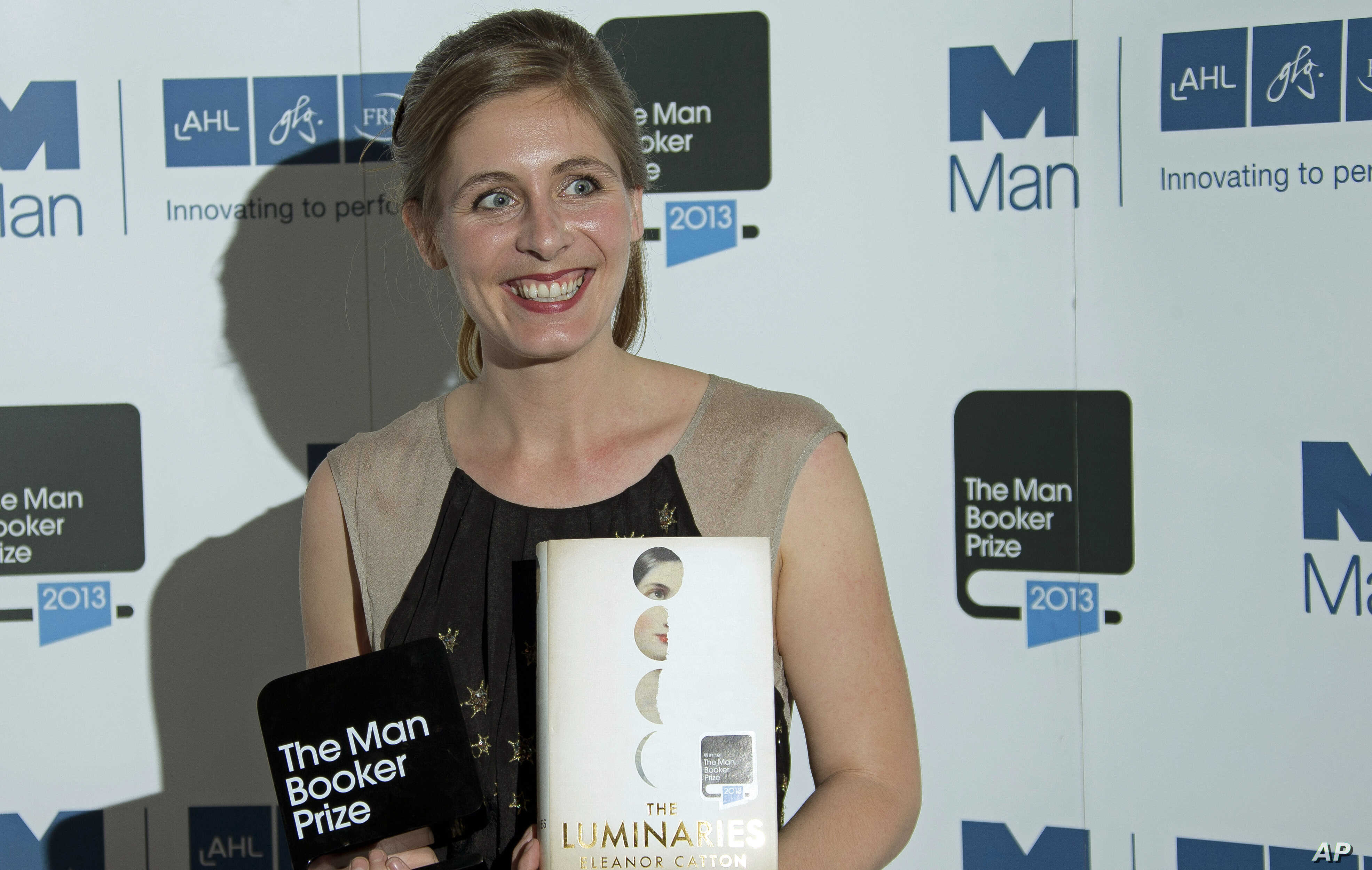 New Zealand writer Eleanor Catton poses after being announced the winner of the Man Booker Prize for Fiction, holding her prize and her book for the photographers, in central London, Oct. 15, 2013.