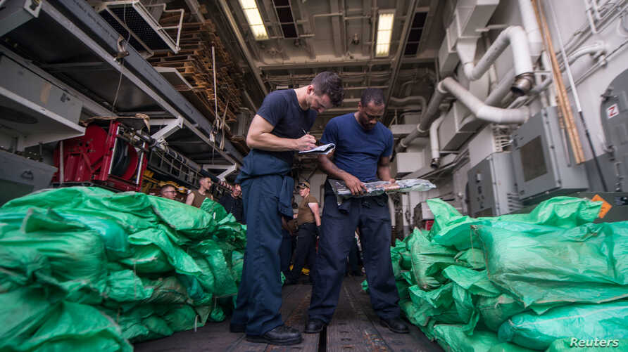 Ensign Sean Standard and Logistics Specialist 2nd Class Ray Sanders take inventory of a cache of more than 1,000 AK-47 automatic rifles in the hangar bay of the guided-missile destroyer USS Jason Dunham, seized from a traditional dow in the Gulf of A