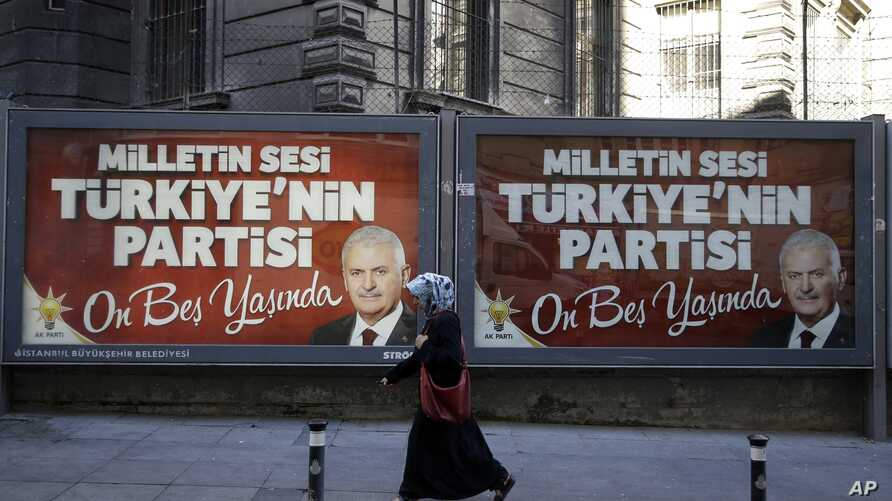 A woman passes a picture of the Turkish Prime Minister Binali Yildirim for the 15th anniversary of AKP party as the sign reads ''The people's voice, Turkey's party, it's now fifteen years old'' in Istanbul, Monday, Aug. 15, 2016.