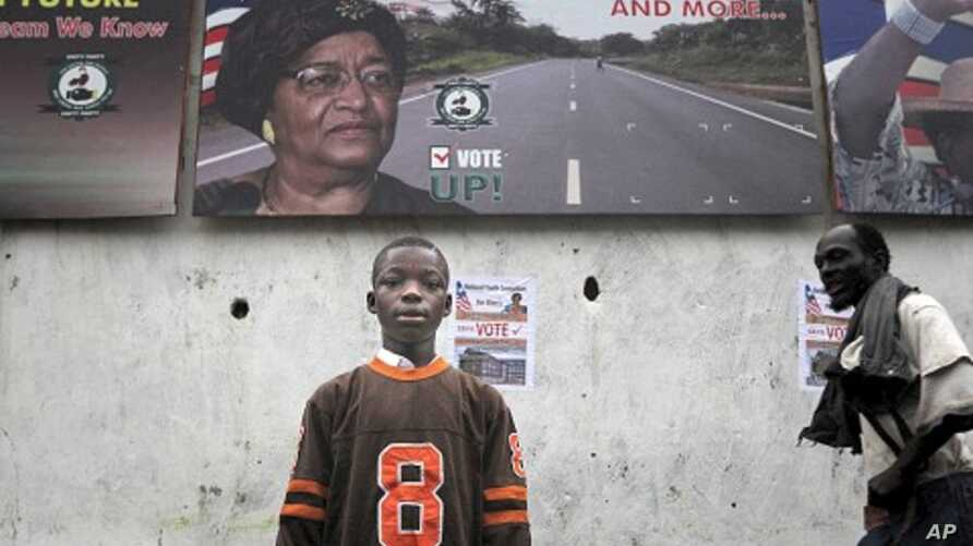 A Liberian child stands in front of an election poster for President Ellen Johnson Sirleaf in the Liberian capital Monrovia, September 8, 2011.