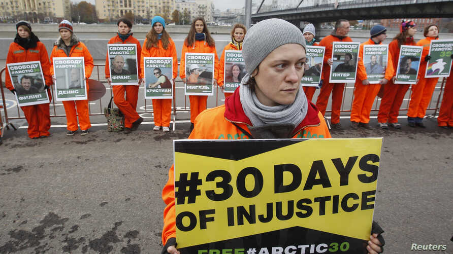 Greenpeace activists hold portraits of those detained on the boat Arctic Sunrise, during a rally in Moscow, Oct. 18, 2013.