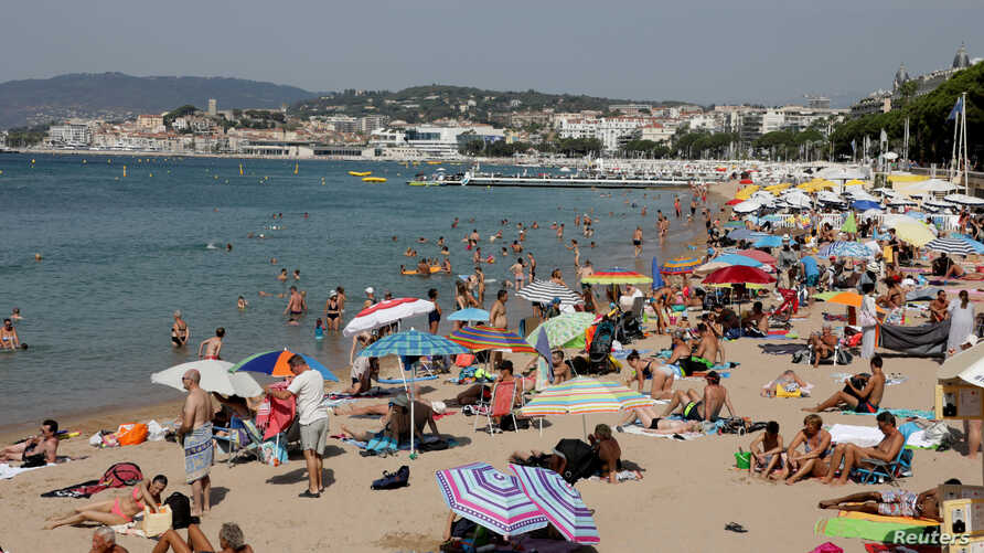 FILE - People enjoy the sun on a Croisette beach in Cannes, France.