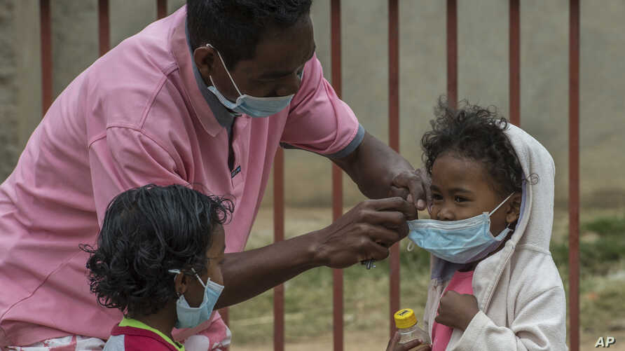Face masks are placed on children in Antananarivo, Madagascar, Oct. 3, 2017. Authorities in Madagascar are struggling to contain an outbreak of plague that has killed at least 20 people, and the government has begun a campaign to disinfect school cla