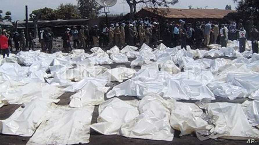 UN Peacekeepers and medics stand beside the bagged bodies of victims of an oil tanker explosion in Sange, Democratic Republic of Congo, 03 Jul 2010